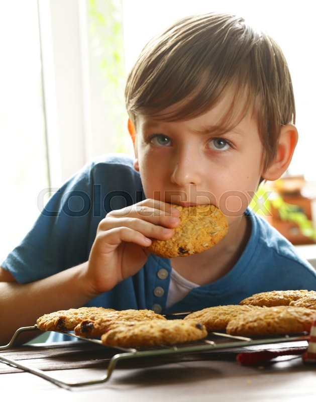 Stock image of 'Blond boy eating oatmeal cookies on kitchen'