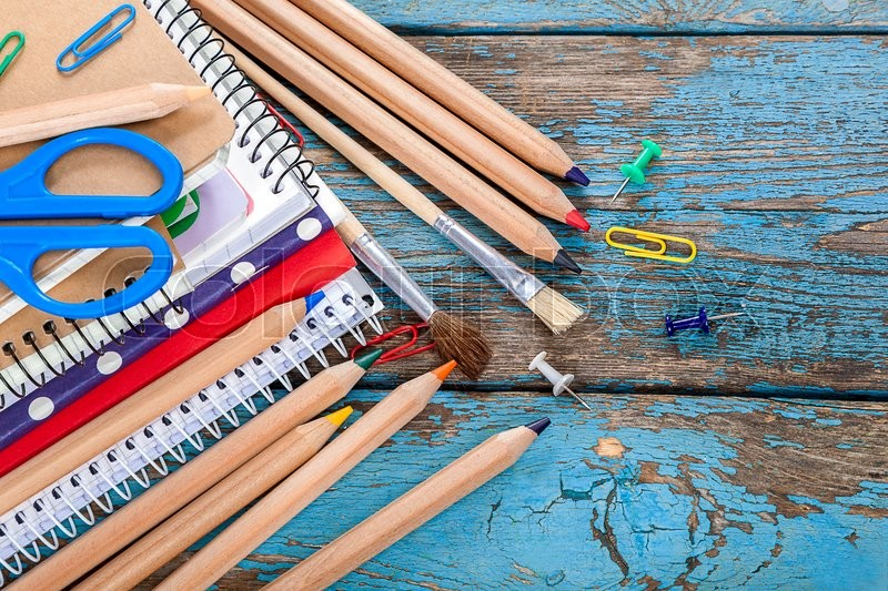 Stock image of 'Notepad, pencils, scissors, paper clips and glasses. Office or school supplies on wooden planks painted in blue.'