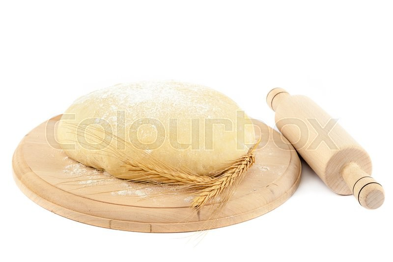 Stock image of 'Dough on the wooden board with ears and a rolling pin isolated on white background.'