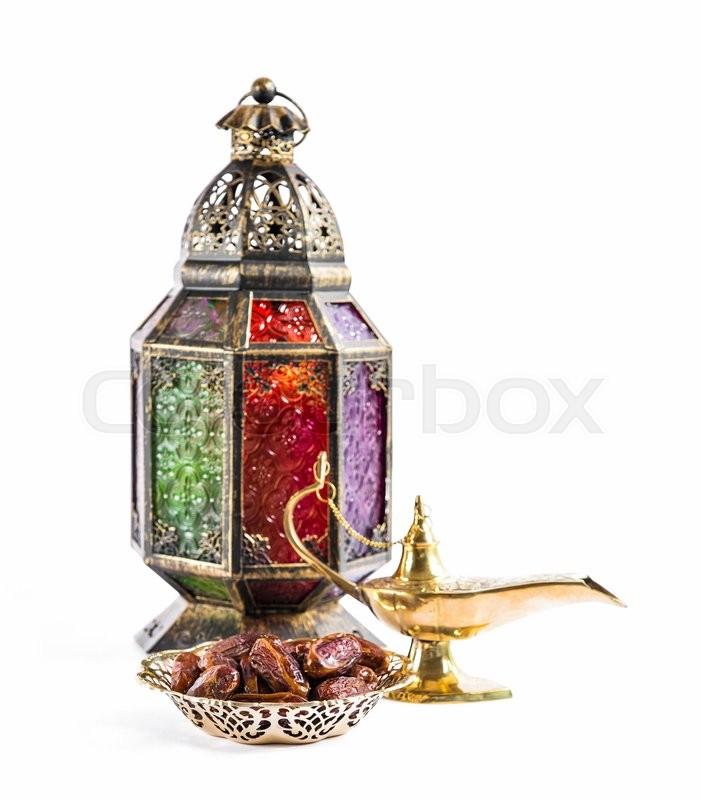 Stock image of 'Oriental vintage light lantern and dates fruits on white background. Arabic holidays decoration. Selective focus'