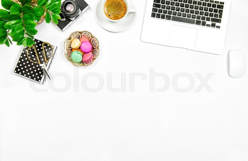 Stock image of 'Creative feminine home office workplace. Coffee, macaroon cookies, laptop computer and green plant on white table background'