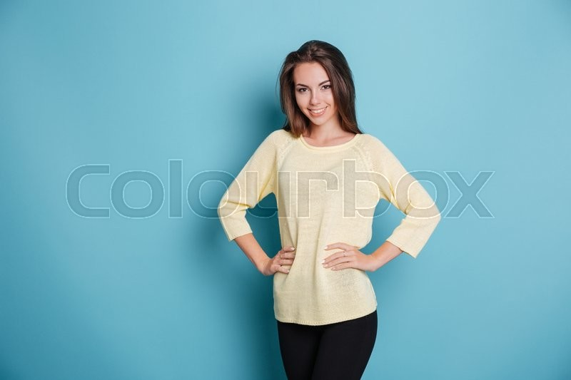 Stock image of 'Portrait of a beautiful smiling girl with her arms on hips isolated on the blue background'