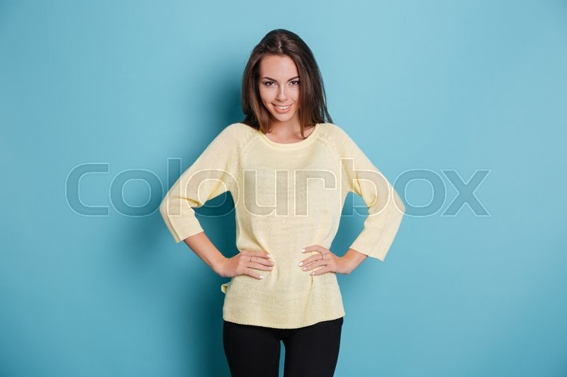Stock image of 'Beautiful condident young girl looking at camera and holding arms on her hips isolated on the blue background'