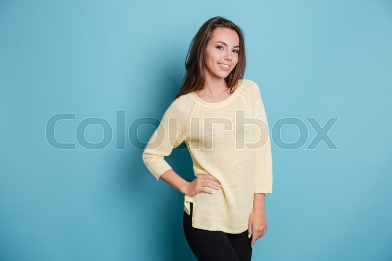 Stock image of 'Beautiful young brunette girl holding her hand on hips isolated on the blue background'