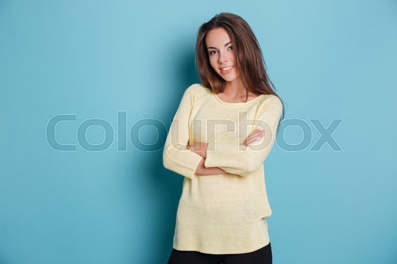 Stock image of 'Beautiful casual woman posing with her arms crossed isolated on the blue background'