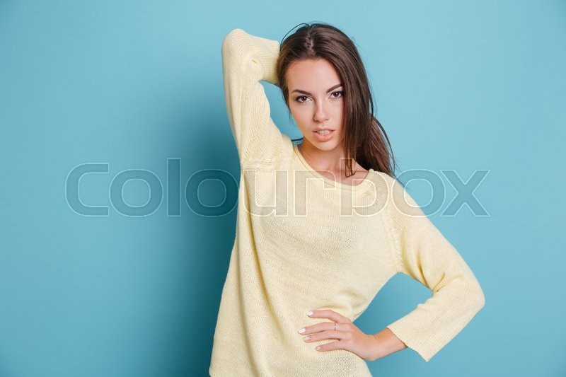 Stock image of 'Beautiful young girl posing and looking at the camera isolated on the blue background'