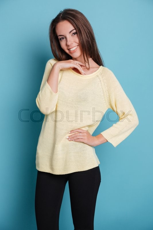 Stock image of 'Pretty young girl standing and looking at the camera isolated on the blue background'