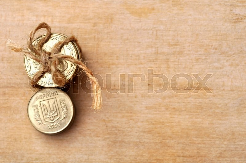 Stock image of 'Golden coins with rope on wooden table'