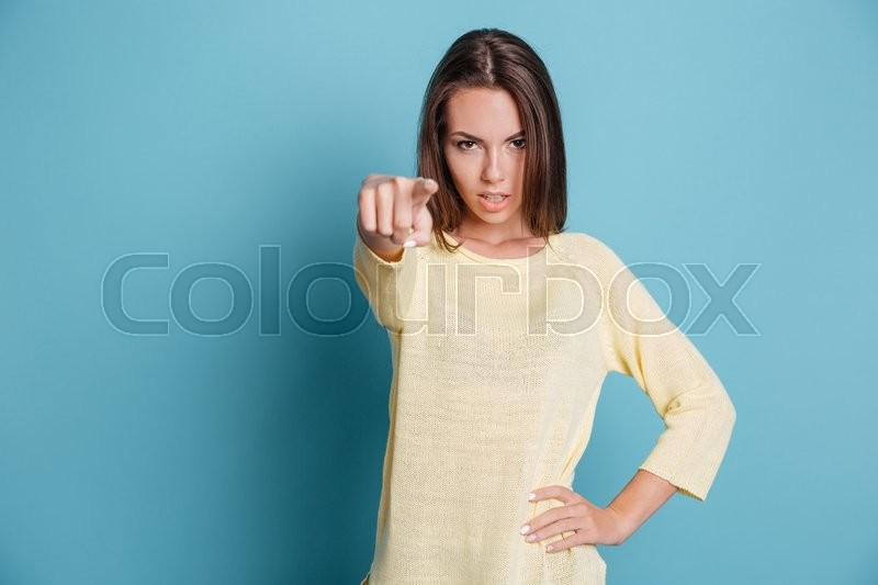 Stock image of 'Beautiful confident girl pointing at camera isolated on the blue background'