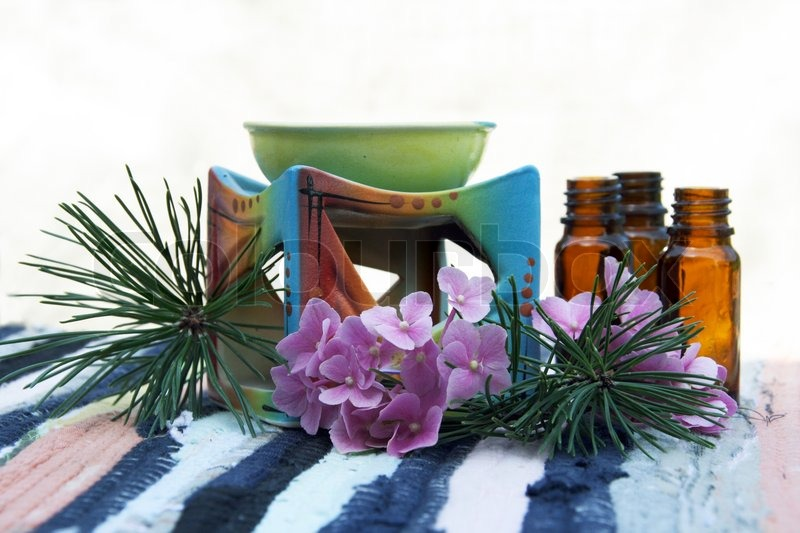 Stock image of 'Aromatherapy Aroma Oil in Glass Bottles and Candle Bowl Decorated'