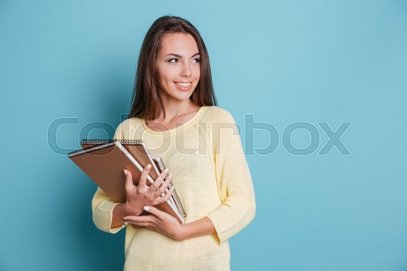 Stock image of 'Portrait of beautiful young smiling brunette holding notebooks isolated on the blue background'