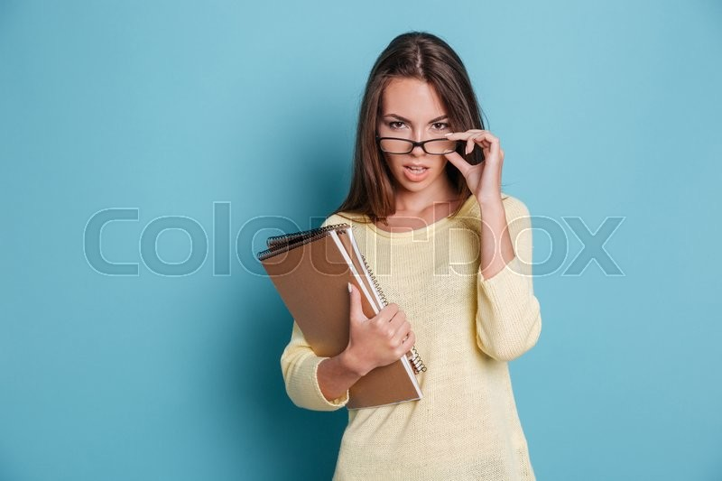 Stock image of 'Smart beautiful woman looking at camera and touching glasses isolated on the blue background'