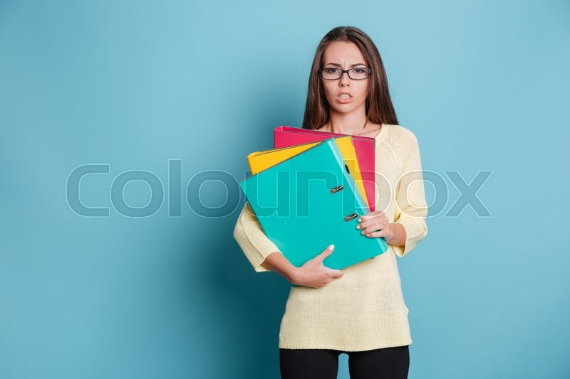Stock image of 'Concentrated young woman holding binders isolated on the blue background'