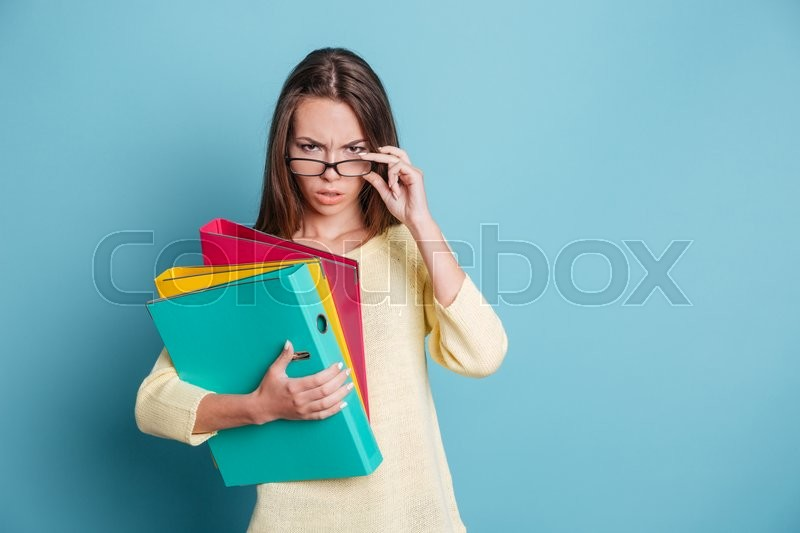Stock image of 'Seriously looking smart girl holding colorful binders isolated on the blue background'