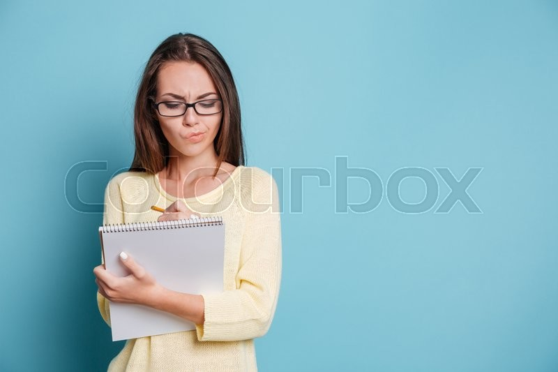 Stock image of 'Serious pensive young girl making notes in the notebook isolated on the blue background'