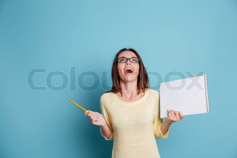 Stock image of 'Laughing cheerful pretty girl holding notebook isolated on the blue background'