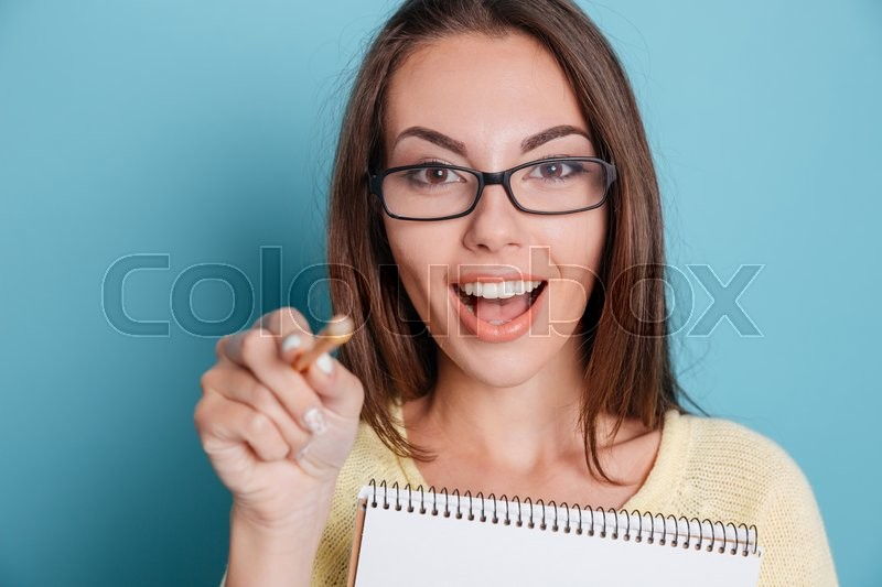 Stock image of 'Close-up of a cute young girl pointing at camera holding notebook over blue background'