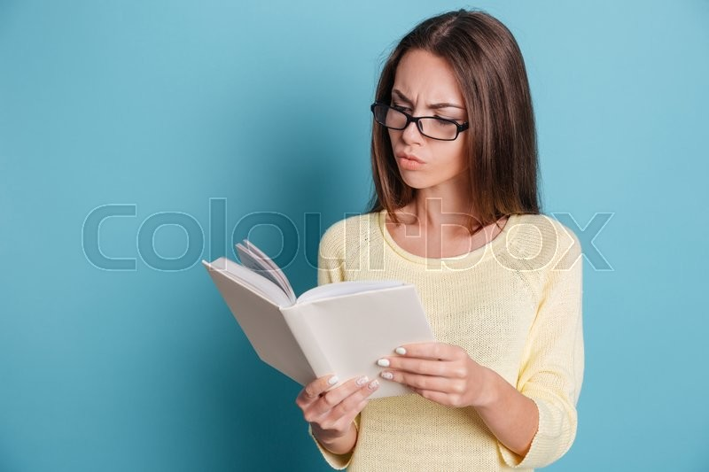 Stock image of 'Pensive smart young girl reading book isolated on the blue background'