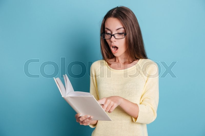 Stock image of 'Surprised amazed beautiful girl looking at the book isolated on the blue background'