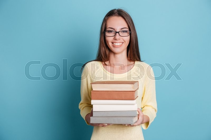 Stock image of 'Cute smiling girl holding many books isolated on the blue background'