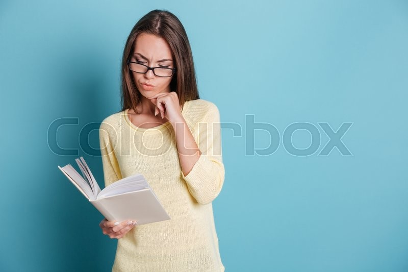 Stock image of 'Beautiful pensive young girl in eyeglasses reading book over blue background'