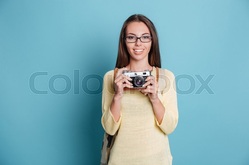 Stock image of 'Young pretty girl taking photo using camera isolated on the blue background'