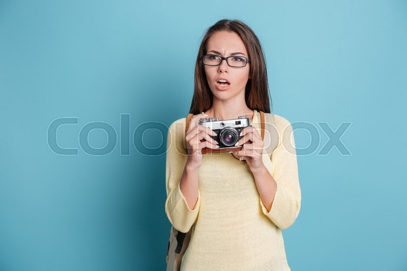Stock image of 'Pensive beautiful girl with photocamera isolated on the blue background'
