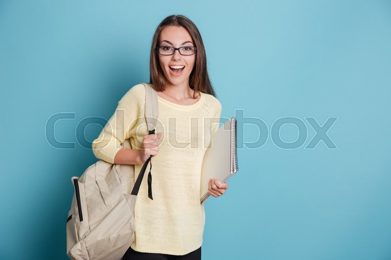 Stock image of 'Beautiful cheerful smiling girl holding bagpack and notebook isolated on the blue background'
