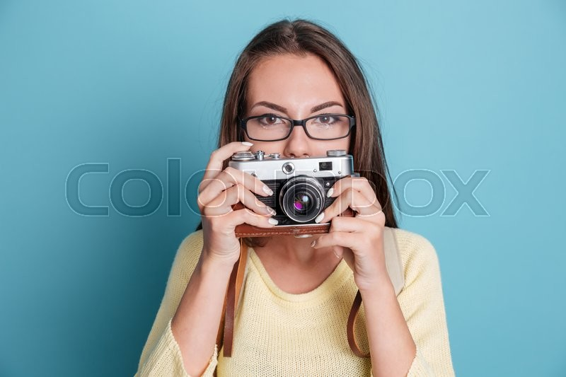 Stock image of 'Beautiful young pretty woman with photo camera isolated on the blue background'