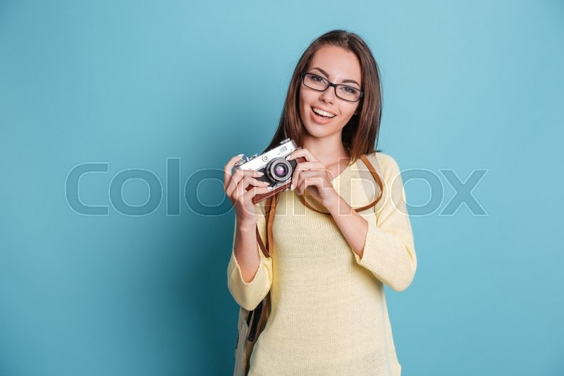Stock image of 'Young pretty girl taking photo using photocamera isolated on the blue background'