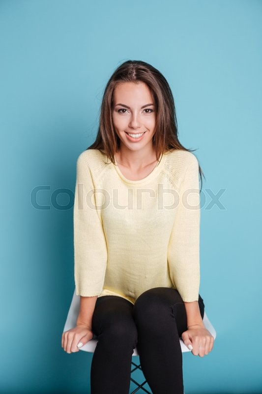 Stock image of 'Close-up portrait of a nice beautiful smiling girl sitting on chair isolated on the blue background'
