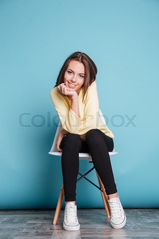 Stock image of 'Young woman sitting on the chair hand under chin isolated on the blue background'