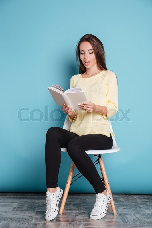 Stock image of 'Pensive young attractive girl reading book and sitting on chair isolated on the blue background'