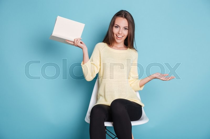Stock image of 'Pretty funny young girl with a book sitting on chair isolated on the blue background'