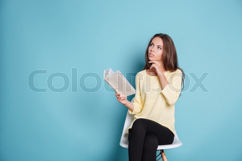 Stock image of 'Pensive smart young girl thinking about something isolated on the blue background'