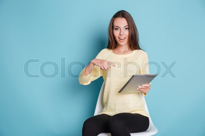 Stock image of 'Funny young smiling girl pointing at pc tablet computer isolated on the blue background'