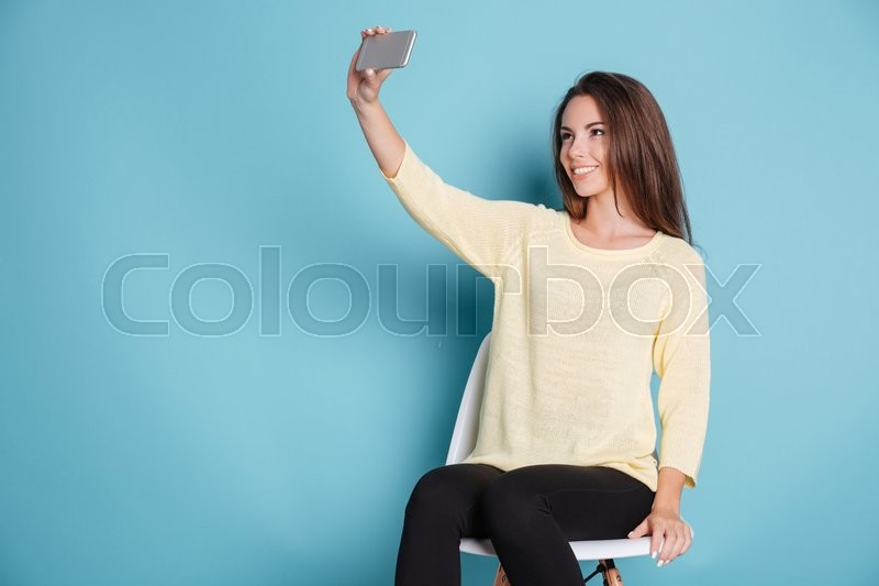 Stock image of 'Pretty young girl making selfie using smartphone isolated on the blue background'