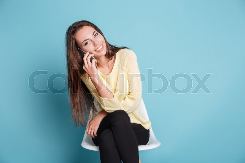 Stock image of 'Portrait of a smiling young woman talking on the phone and looking at camera isolated on a blue background'