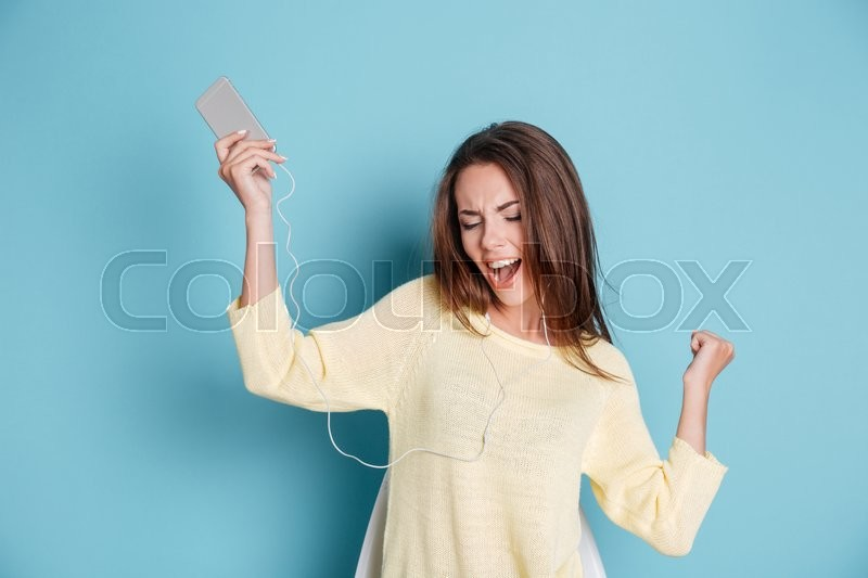 Stock image of 'Young beautiful woman with headphones dancing isolated on blue background'