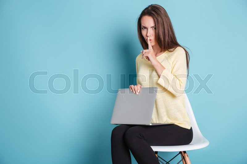 Stock image of 'Serious pretty woman making silence gesture using laptop isolated on the blue background'