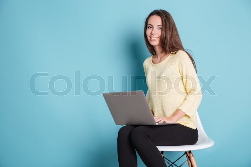 Stock image of 'Smiling pretty teen with laptop pc computer isolated on the blue background'