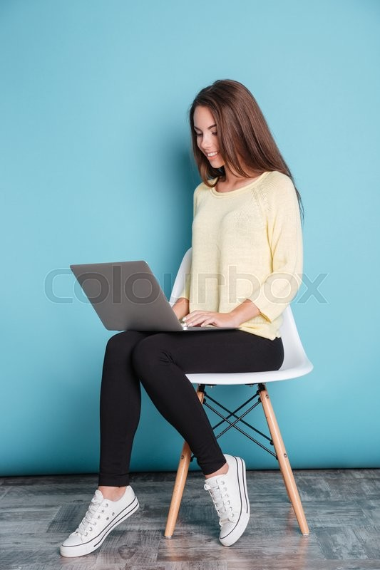 Stock image of 'Young beautiful smart girl using laptop pc computer for study isolated on the blue background'