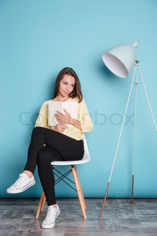 Stock image of 'Young beautiful girl dreaming about something and holding book isolated on the blue background'