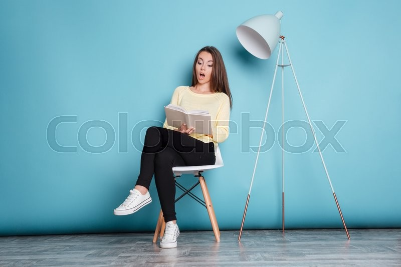 Stock image of 'Shocked pretty girl looking at the book and sitting on the chair isolated on the blue background'