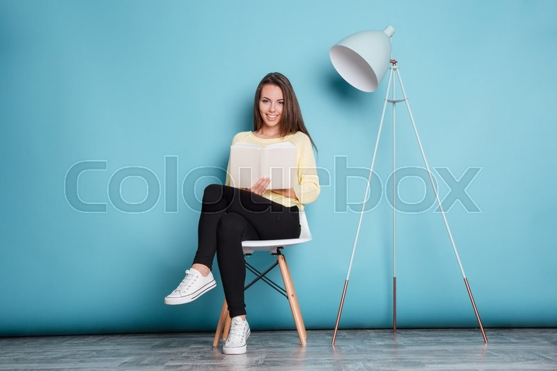 Stock image of 'Smiling pretty woman looking at camera and holding book isolated on the blue background'