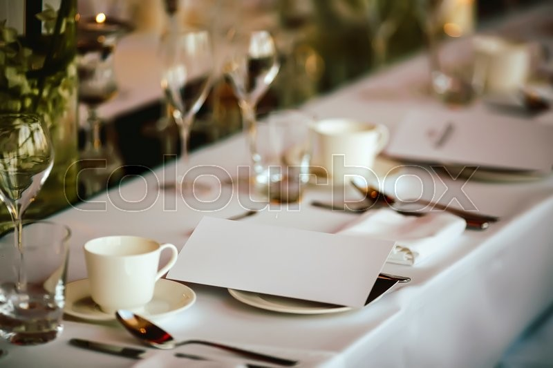 Stock image of 'Table setting at wedding. Steampunk style. Glasses. plates, cutlery on craft paper with candlelights on background.'