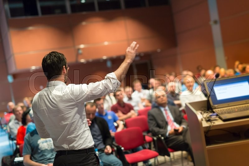 Stock image of 'Speaker giving a talk on corporate Business Conference. Audience at the conference hall. Business and Entrepreneurship event.'