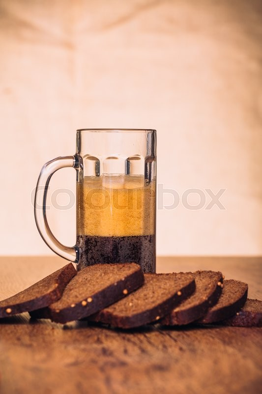 Stock image of 'Russian brew in mug  and loaf of rye flour on wooden background'