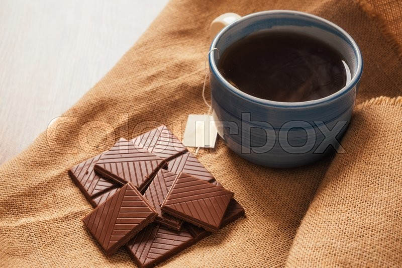 Stock image of 'blue cup of tea and a chocolate bar  on a background of burlap'