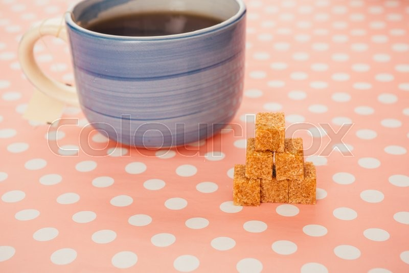 Stock image of 'blue cup of tea and lump sugar on pink  background'